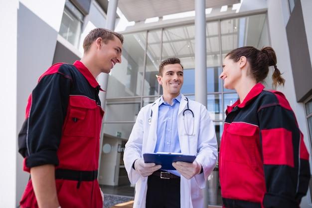 Doktor spricht mit sanitäter im korridor