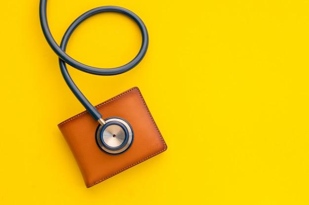 Doktor stethoskop und die neue brieftasche aus braunem leder für männer auf gelb. budget für gesundheitscheck oder geld- und finanzkonzept