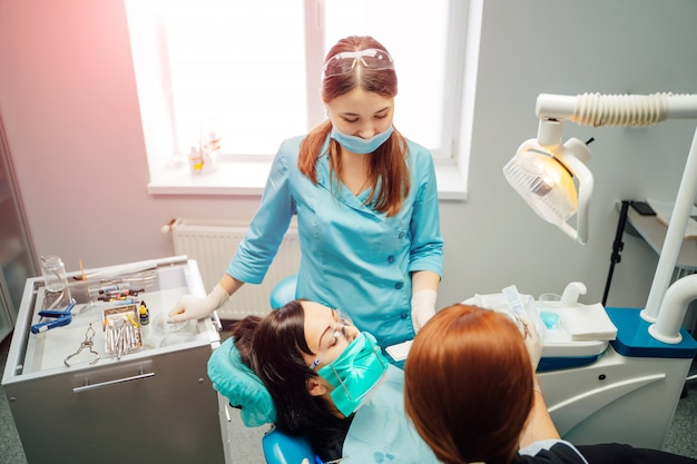 Doktor stomatologist frau und ihre assistentin arbeiten mit einem patienten in der klinik.