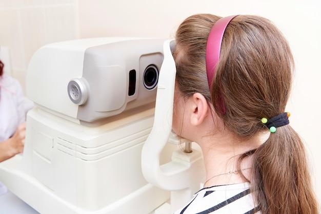 Doktor überprüft augen des kindes mit keratometer