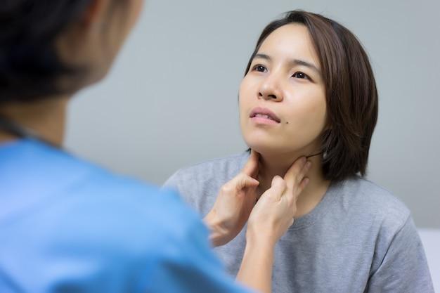 Doktor überprüft den verletzten hals des weiblichen patienten