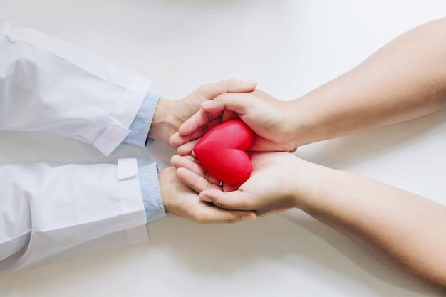 Doktor und der patient, die ein rotes herz zusammenhalten.