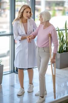 Doktor und eine ältere frau mit einer krücke, die in einem korridor gehen und sprechen
