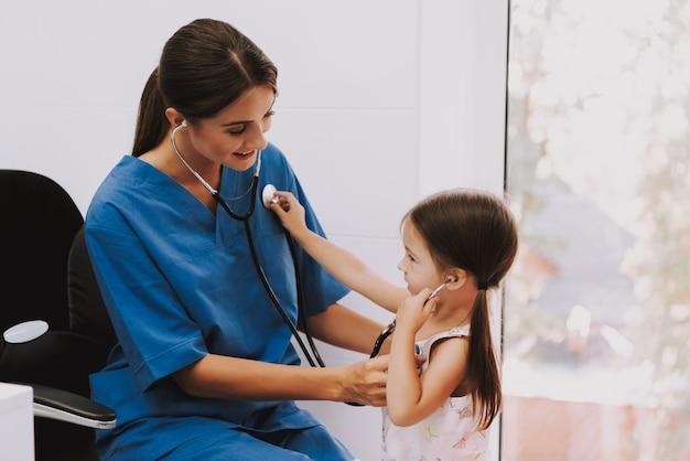 Doktor und kind hören sich durch stethoskop.
