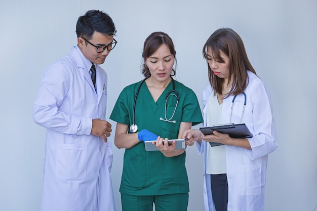 Doktor und krankenschwester, die geduldige informationen auf einem tablettengerät überprüfen