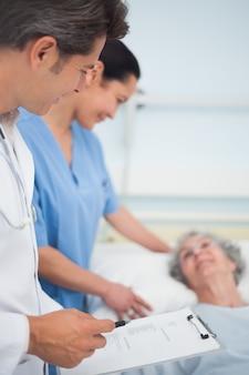 Doktor und krankenschwester, die nahe bei einem patienten stehen