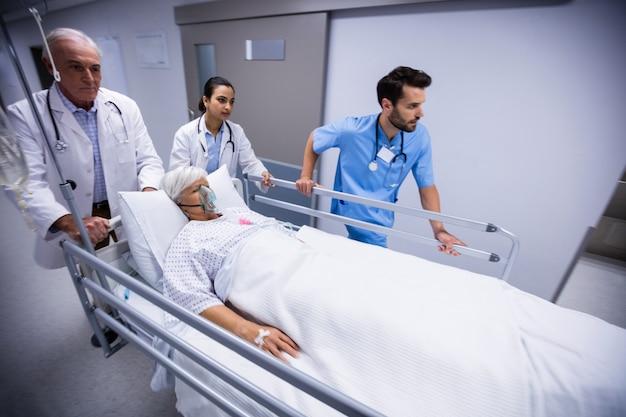 Doktor und krankenschwester schieben notbahre bett im korridor