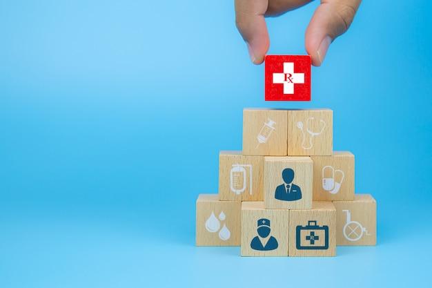 Doktor und patient auf würfelholzspielzeugblöcken mit medizinischer ikone