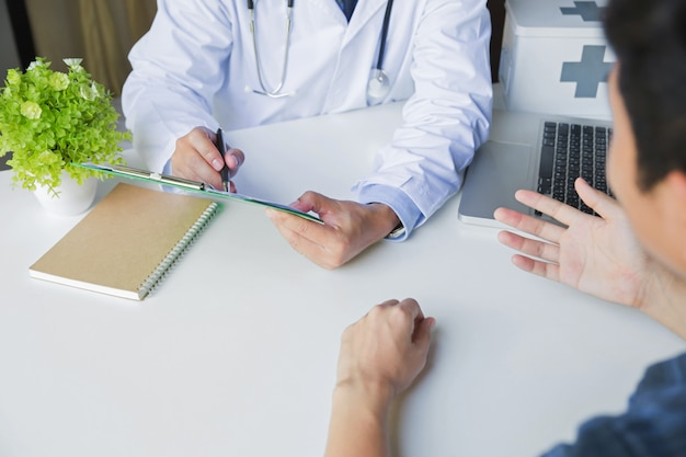 Doktor und patient, die etwas am schreibtisch im krankenhausbüro besprechen.