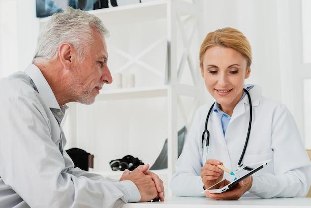 Doktor und patient, die tablette betrachten