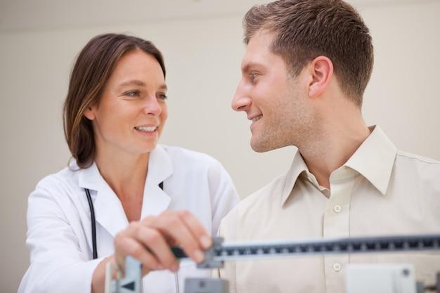 Doktor und patient, die über gewichtsmessung sprechen