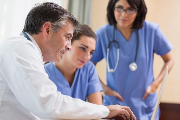 Doktor und zwei krankenschwestern, die laptop betrachten
