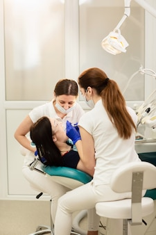 Doktor whitassistent, der zähne des patienten, karies verhindernd behandelt. stomatologie-konzept