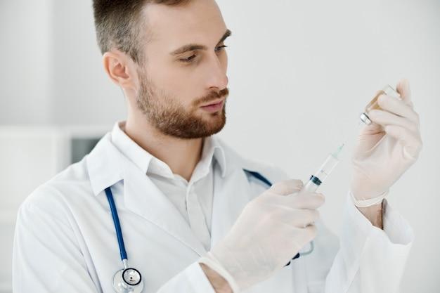 Doktor widoctor mit einer spritze in der hand und war ein impfstoff schutzhandschuhe licht hintergrund ampulle in der hand. hochwertiges foto
