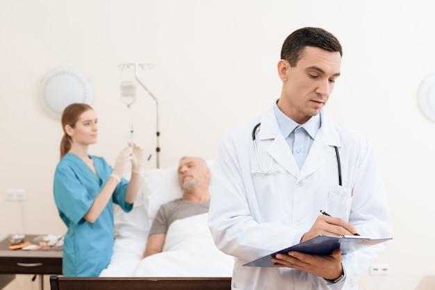 Doktor wirft auf kamera auf, während krankenschwester tropfenzähler vorbereitet.