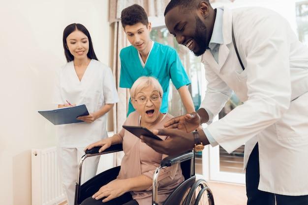 Doktor zeigt einem älteren patienten etwas auf der tablette.