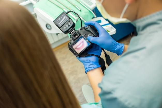 Doktor zeigt mädchen ein bild ihrer zähne vor der kamera