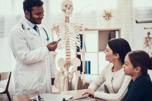 Doktor zeigt mutter und tochter das skelett.
