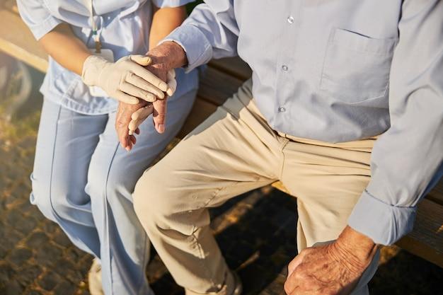 Doktorarzt, der die hand eines alten patienten hält
