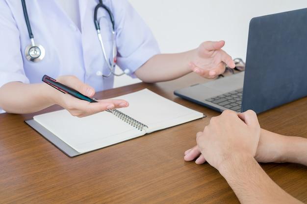 Doktorarzt, der mit männlichen patienten im krankenhausprüfungsraum sich berät. gesundheitskonzept der männer