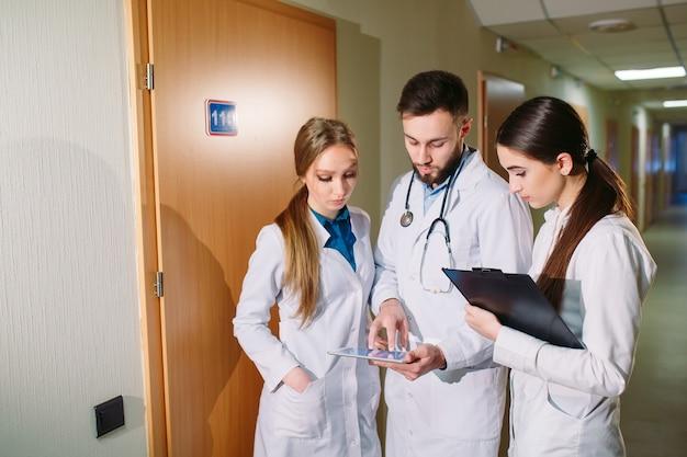 Doktoren, die das kardiogramm des patienten auf der tablette besprechen.