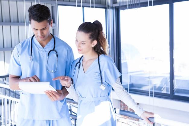 Doktoren, die digitale tablette im krankenhauskorridor verwenden
