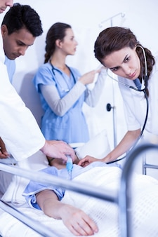 Doktoren, die einen patienten auf bett im krankenhaus überprüfen
