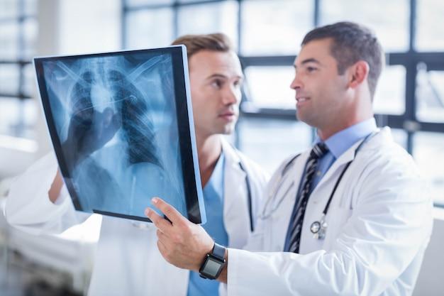 Doktoren, die einen röntgenstrahl am krankenhaus besprechen