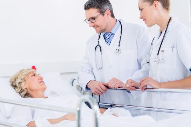 Doktoren, die einen weiblichen patienten im krankenhaus besuchen