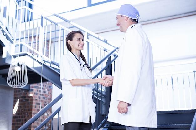Doktoren, die hände auf treppenhaus im krankenhaus rütteln