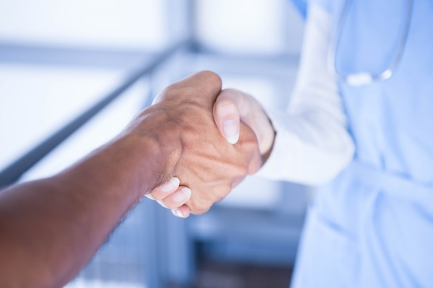 Doktoren, die hände im krankenhausflur rütteln