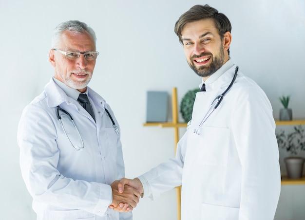 Doktoren, die hände rütteln und kamera betrachten