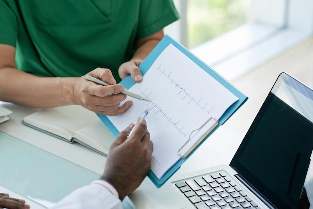 Doktoren, die kardiogramm ihres patienten betrachten