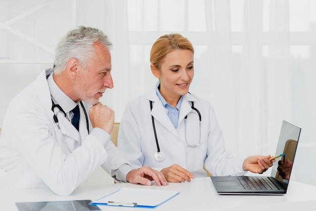 Doktoren, die laptop beim sitzen betrachten