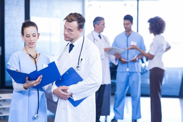 Doktoren, die medizinischen report betrachten und eine diskussion haben