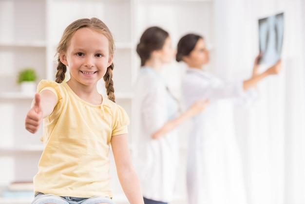 Doktoren, die röntgenstrahl des kleinen patienten an der klinik besprechen.