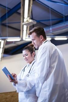 Doktoren, die über digitaler tablette im krankenhaus sich besprechen