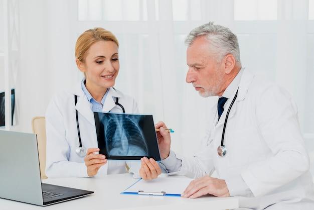 Doktoren, die zusammen röntgenstrahl betrachten