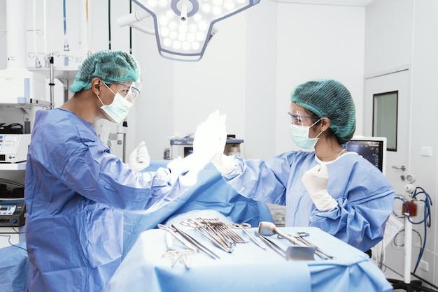 Doktoren und krankenschwester tun hallo fünf, nachdem sie von operation im operationsraum gefolgt sind