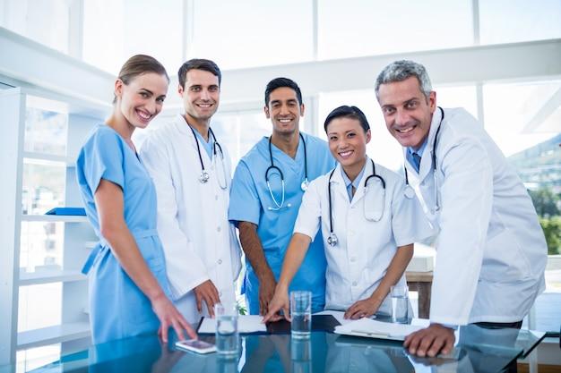 Doktoren und krankenschwestern, die an der kamera lächeln