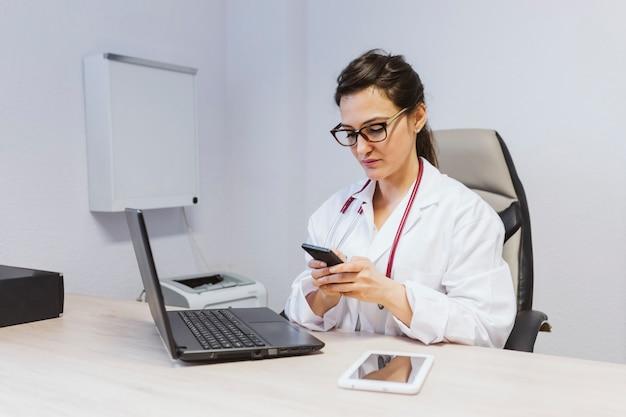 Doktorfrau, die an laptop am konsultieren arbeitet