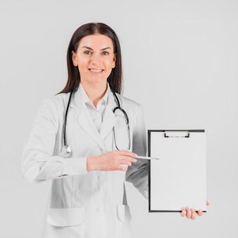 Doktorfrau, die auf klemmbrett darstellt