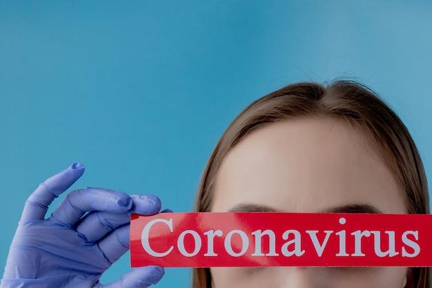 Doktorfrau, die auf rotes papier mit mesaage coronavirus auf blauem hintergrund zeigt