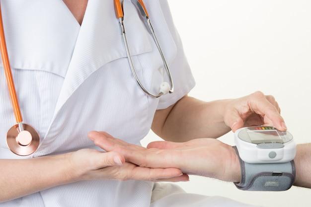 Doktorfrau, die den arteriellen blutdruck misst