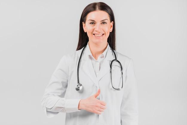 Doktorfrau, die oben daumen lächelt und gestikuliert