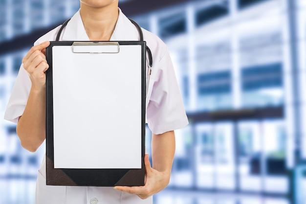 Doktorfrau hält leeres arbeitsbrett im krankenhaus