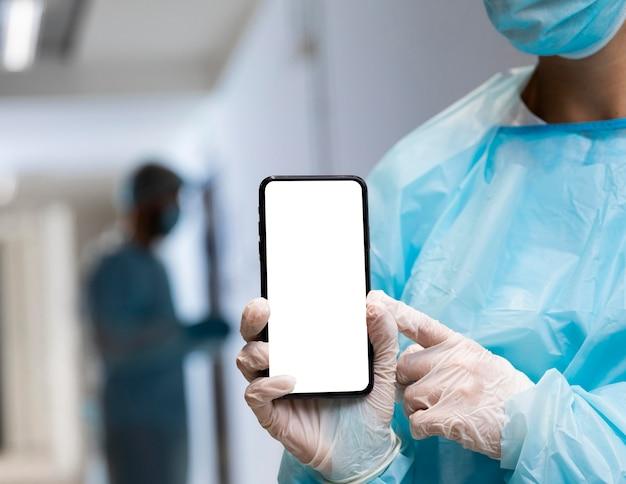 Doktorfrau in der schutzkleidung, die auf ein smartphone zeigt