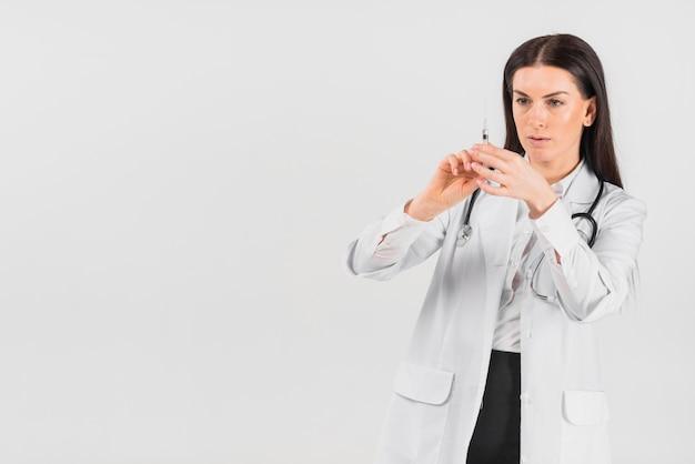 Doktorfrau mit ernstem gesicht, das impfung hält