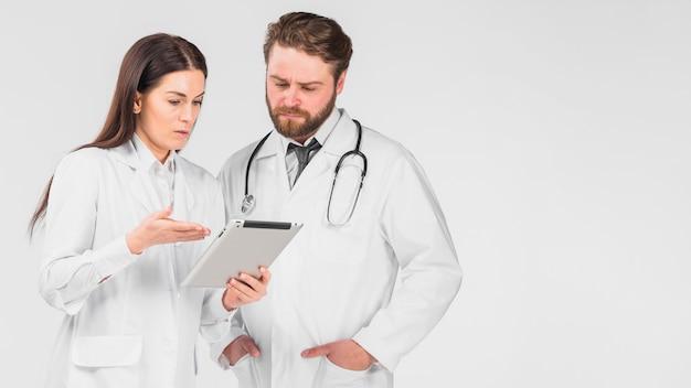 Doktorfrau und -mann, die tablette betrachten