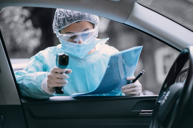 Doktorfrau verwenden infrarot-stirn-thermometer-pistole, um die körpertemperatur zu überprüfen.